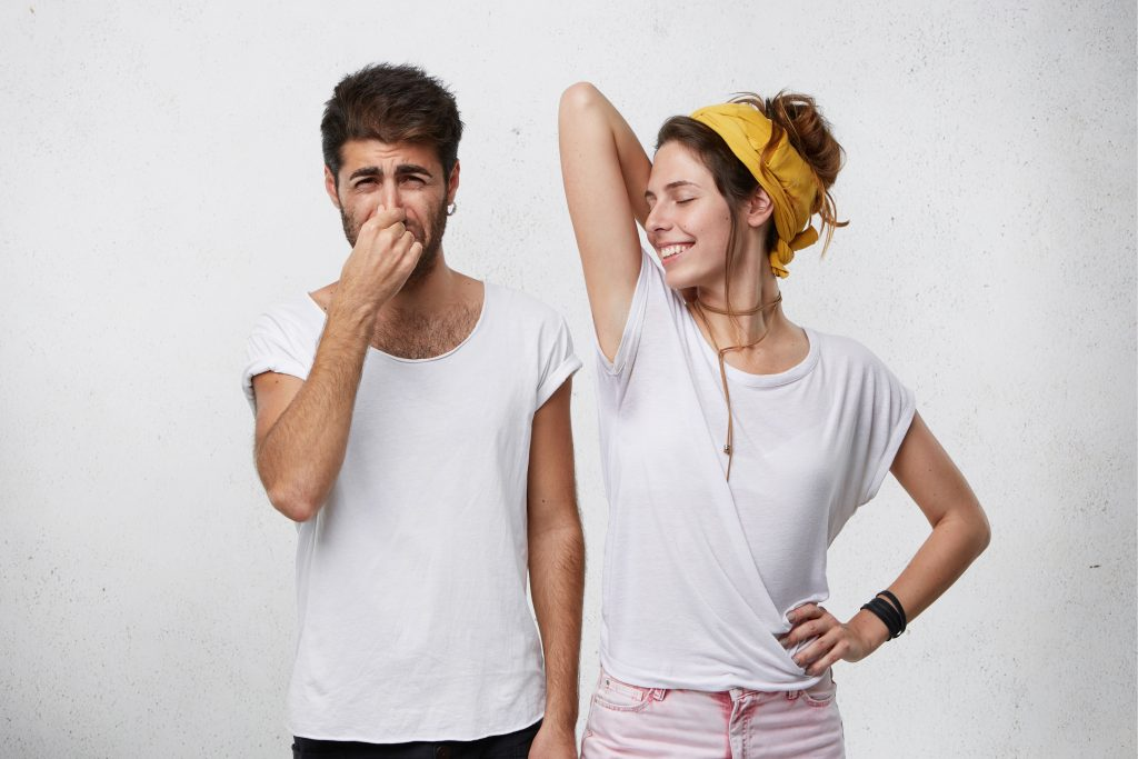 problems with body odor disgusted male pinching his nose feeling bad smell or stink coming out from attractive smiling girl who is raising her arm showing wet t shirt because of armpit sweat